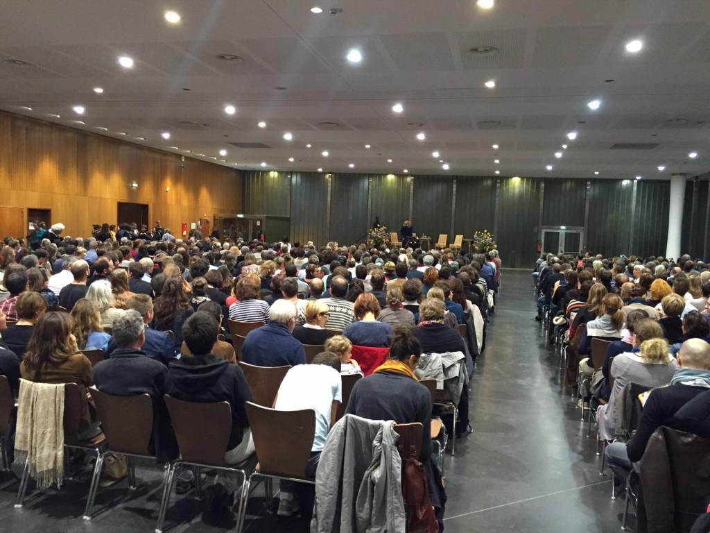 Une foule dense et attentive de près d'un millier de personnes dans la grande salle des Tanzmatten.